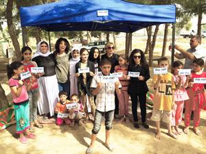 道路脇で野宿していた避難民にテント、食料、ガスコンロ、石けん、紙おむつ、粉ミルク、マットレスなどを配付。左から4人目が筆者(ドホーク、2014年8月)