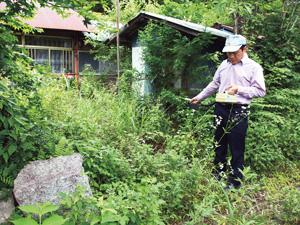 集落の放射線を測定する今野邦彦さん(2016年7月)