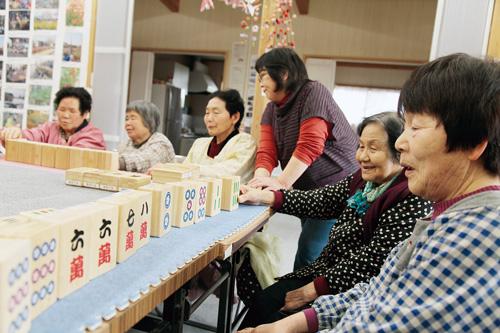 体も動かせる巨大な牌で、麻雀を楽しむ飯舘村の避難者。中央が長谷川さん=伊達市の仮設住宅