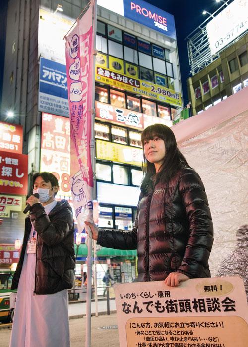 今年3月に行われたJR中野駅前の「なんでも相談会」夕暮れのネオンのもと、道行く人に声をかける