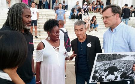 キング牧師の演説場所に立つバクレー監督と松元ヒロさん(右から2人目)