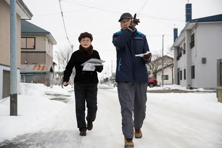 転ばないように気を付けながら歩く有田さん(右)と進藤さん