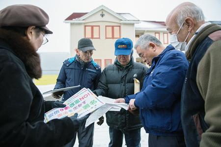 地図で訪問先を確認。右から丸山さん、飯田さん、工藤勝男さん
