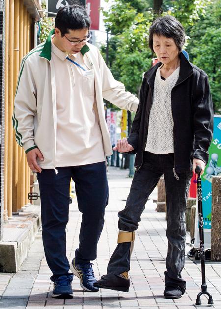 「腰を動かして足を出すイメージで。そうです、いいですね」。声をかけながら樋口惠子さんの歩行訓練を行う矢口さん(左)。脳出血により右片麻痺になった樋口さんは、今は好きだったお酒を断っていますが「温泉に行っておいしいお酒を飲むことが目標なの」と、リハビリに励んでいる