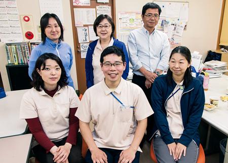 """王子訪問看護ステーションの同僚と。所長の秦陽子さん(前列左)は「矢口さんは家のことも仕事もしっかりやる人ですよ。""""頼れる雰囲気""""がさらに出ることを期待しています」と笑顔。お昼ごはんはみんなで一緒に食べるという、アットホームな雰囲気のステーションです"""