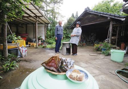 あくまきを煮込む釜戸の前にて。下八重光子さんと夫の一郎さん