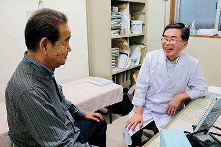 「ある日ね、健診を受けているかと聞かれて『受けてない』と答えたら、すぐに衣笠診療所から電話がかかってきたんだよ。さすが民医連だね」。主治医の岡田哲郎医師と笑い合う山崎さん