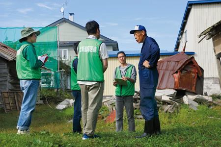 堀合さん(右端)の話を聞く北海道民医連の職員、右は崩れたサイロ