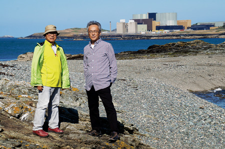 原発建設予定地前に立つ馬場さん(左)と根本さん。遠くに見えるのが廃炉作業中のウィルファA原発