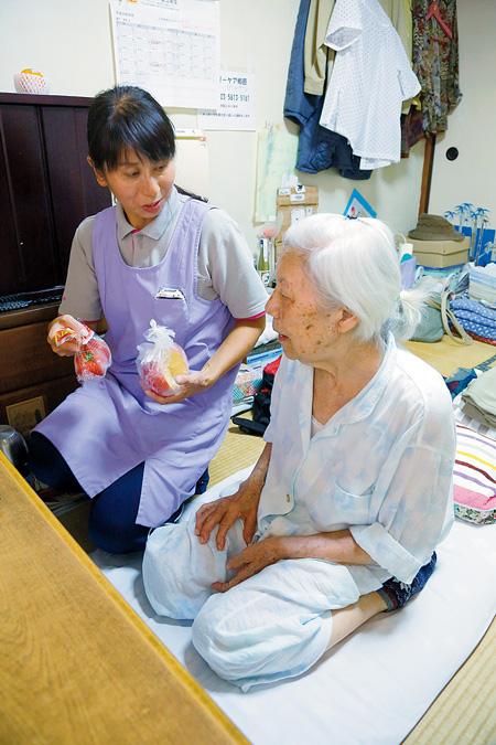 栄子さん(右)と夕食の相談をするヘルパーの相木明子さん