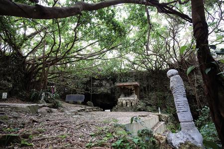 集団自決が行われたチビチリガマには、県内外から多くの人が慰霊に訪れる。奉納された野仏(右)