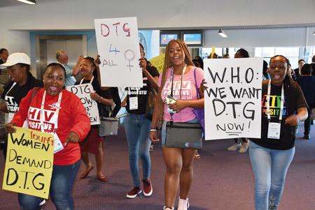 「必要とする全ての女性たちにHIV治療薬を」などのプラカードを掲げ、会場内をデモ行進する患者・感染者たち。胸に「HIV POSITIVE」と描いたTシャツを着ている