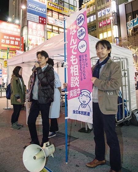 マイクで呼びかける松本さん(左)。周囲のネオンに照らされ、駅前は明るい