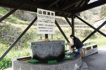 鹿鳴越連山から湧き出る清水を汲むことができる山田湧水
