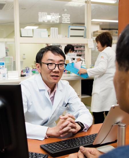 窓口で患者の相談にのる坂井直之さん。ふれあい豊田薬局で