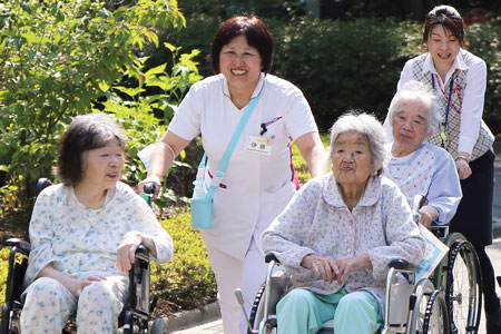 車いすを押しながら患者に笑顔で話しかける伊藤さん(中央) 院内には多くの緑があり、気持ちがいい