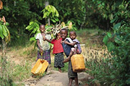 カカオ畑の坂を登りながら、川へ水汲みに行く子どもたち