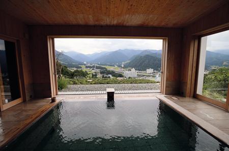 岩原高原に佇む「ホテルシェラリゾート湯沢」。湯船から町の景色が一望できる