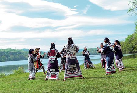 ポロト湖の湖畔で伝統舞踊を舞う人たち(公益財団法人アイヌ民族文化財団提供)