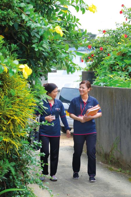 患者宅への小路を歩く寺原さん(左)と常山さん。ハイビスカスが咲いていた
