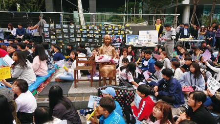 多くの若者が座り込む韓国の「水曜集会」。中央が平和の少女像