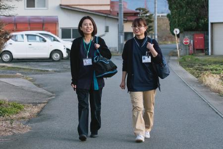 奥山さんの自宅へ向かう武田さん(左)と庄司さん 背後に蔵王の山々がそびえる