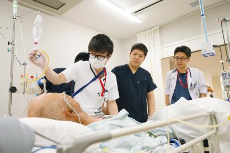 患者を囲んでのカンファレンス。井上賀元医師(右端)と相談しながら点滴を調整する看護師の本田大智さん