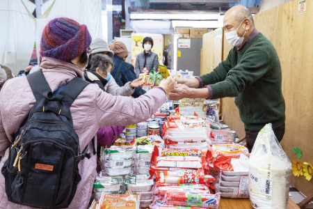 食材を手渡す友の会の南雲副会長(右)