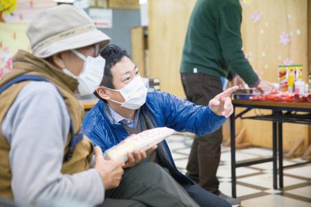 来場者の相談に乗るまくはりの郷の東幹太事務長(右)