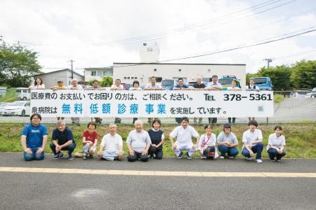 完成した看板前に集合した泉病院の職員と友の会員(大橋愛撮影)
